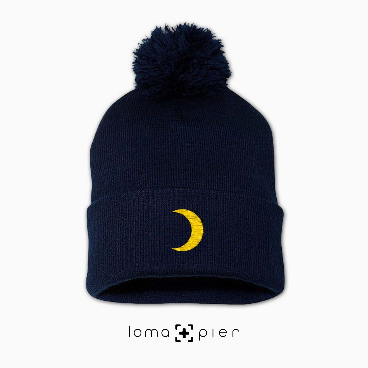 MOON icon embroidered on a navy pom pom beanie by loma+pier beanie store