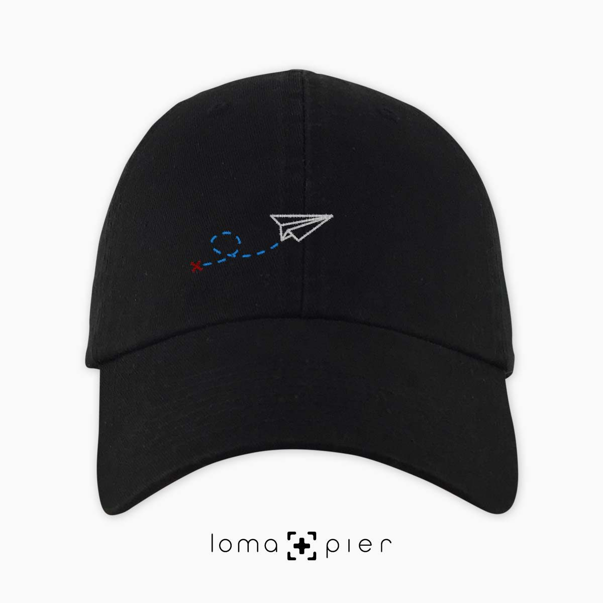 PAPER AIRPLANE icon embroidered on a black dad hat by loma+pier hat store made in the USA
