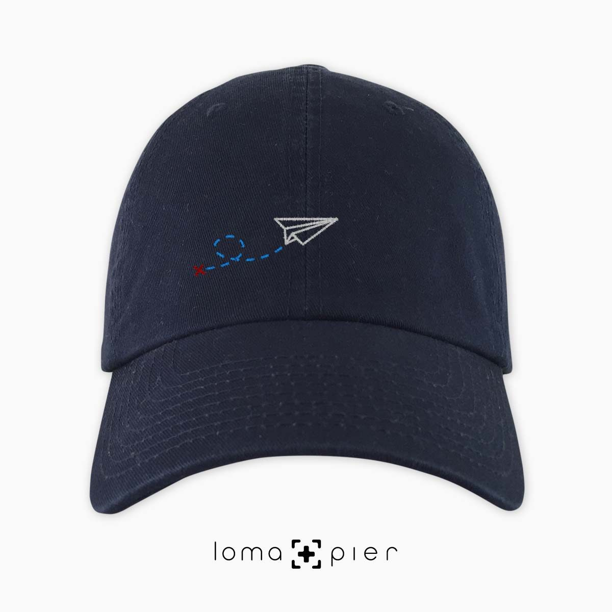 PAPER AIRPLANE icon embroidered on a navy blue dad hat by loma+pier hat store made in the USA