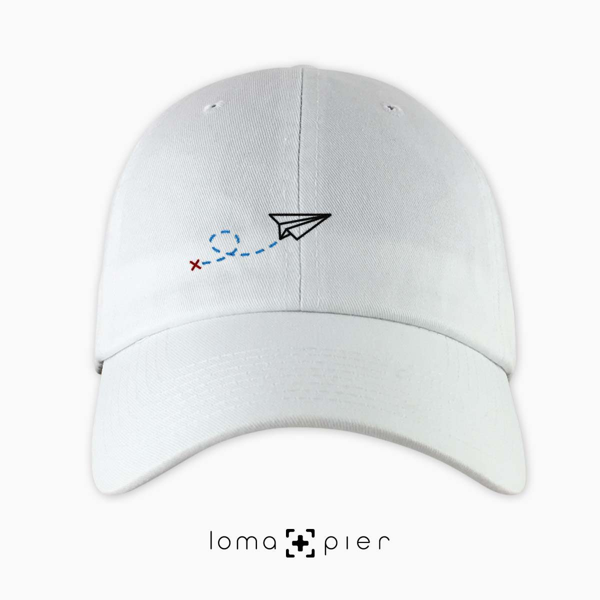 PAPER AIRPLANE icon embroidered on a white dad hat by loma+pier hat store made in the USA