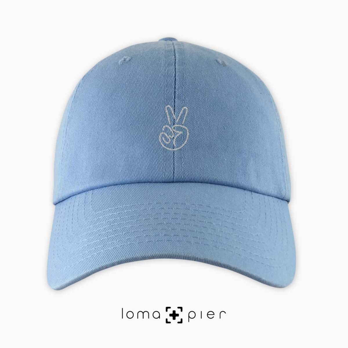 PEACE SIGN HAND icon embroidered on a baby blue unstructured dad hat with white thread by loma+pier hat store made in the USA