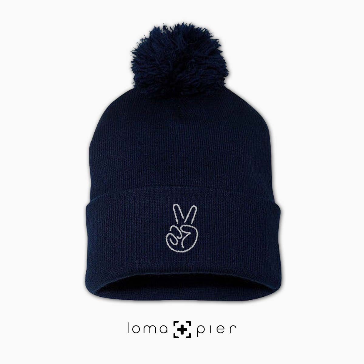 PEACE SIGN HAND icon embroidered on a navy blue pom pom beanie with white thread by loma+pier hat store