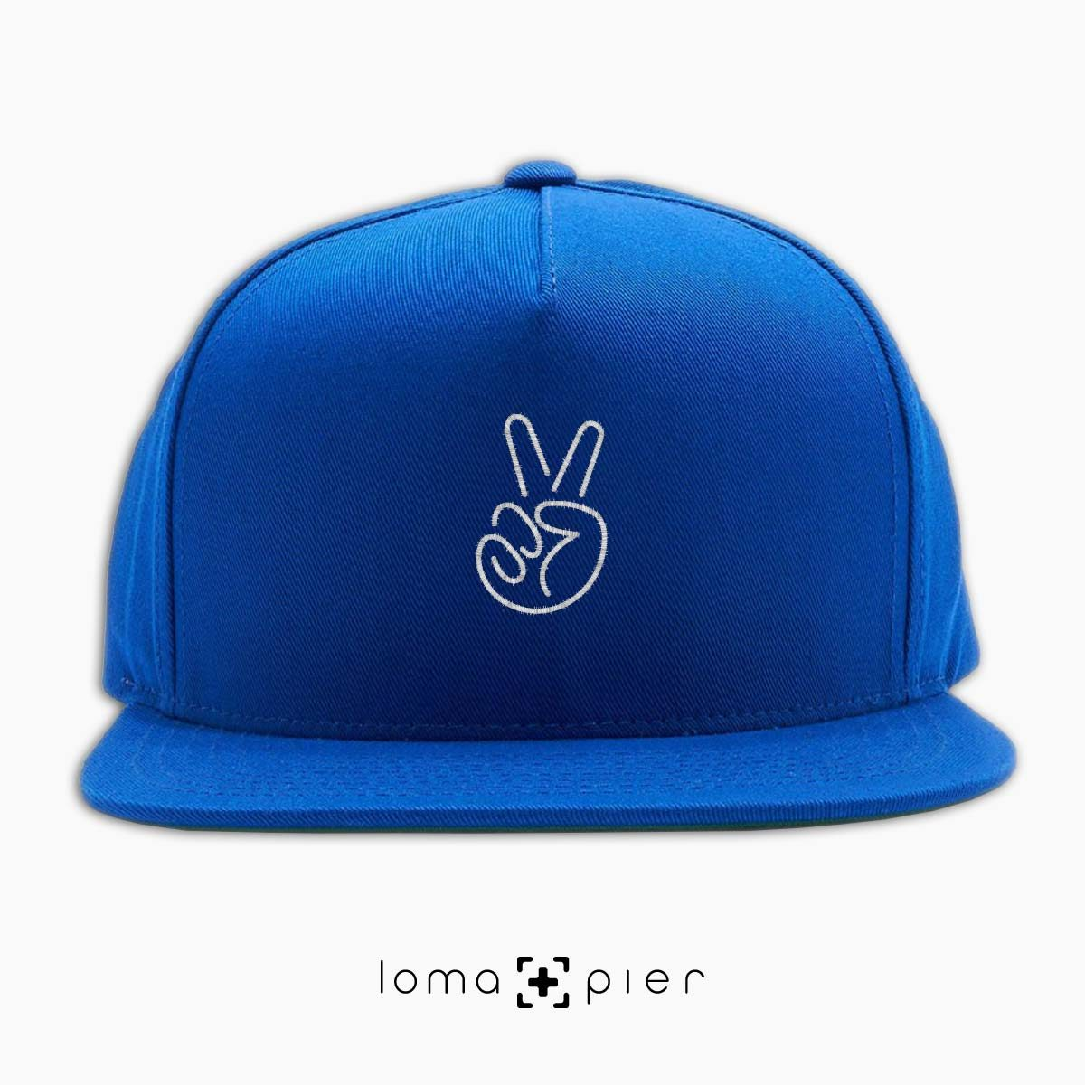 PEACE HAND icon embroidered on a royal blue classic snapback hat with white thread by loma+pier hat store