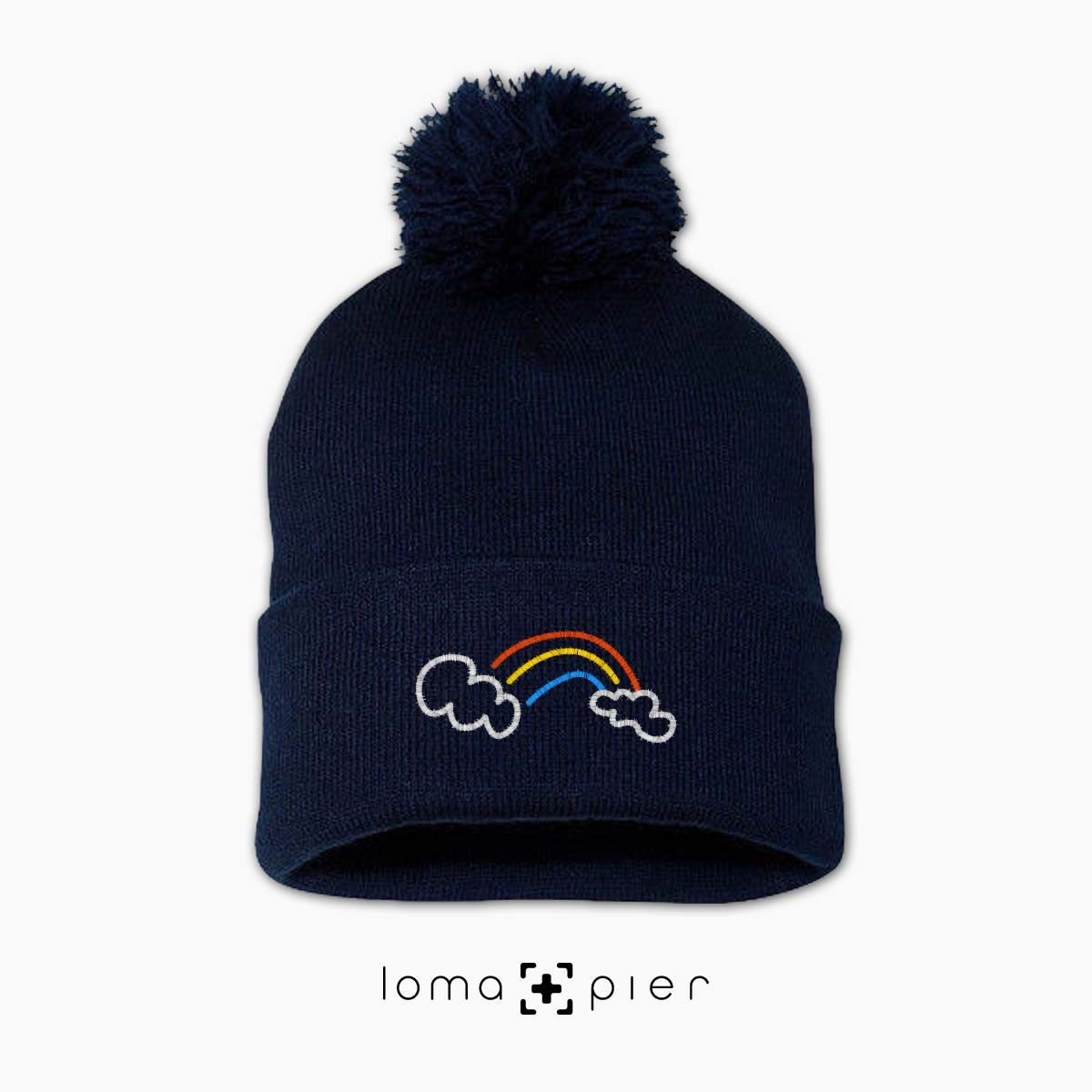 RAINBOW icon embroidered on a navy blue pom pom beanie with white thread by loma+pier hat store