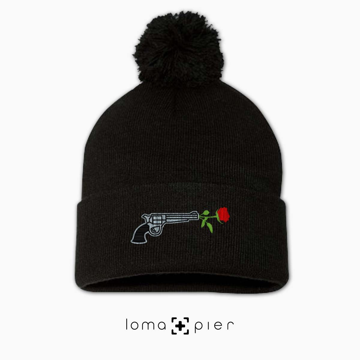 ROSE REVOLVER icon embroidered on a black pom pom beanie with multicolor thread by loma+pier hat store