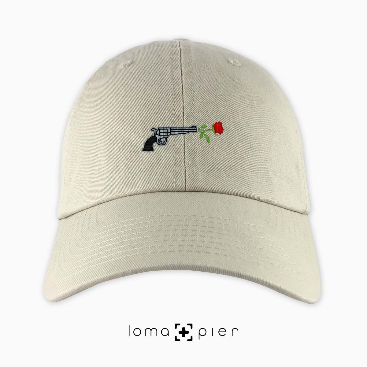 ROSE REVOLVER icon embroidered on a khaki unstructured dad hat with multicolor thread by loma+pier hat store made in the USA