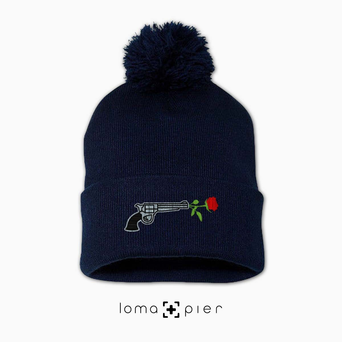 ROSE REVOLVER icon embroidered on a navy blue pom pom beanie with multicolor thread by loma+pier hat store