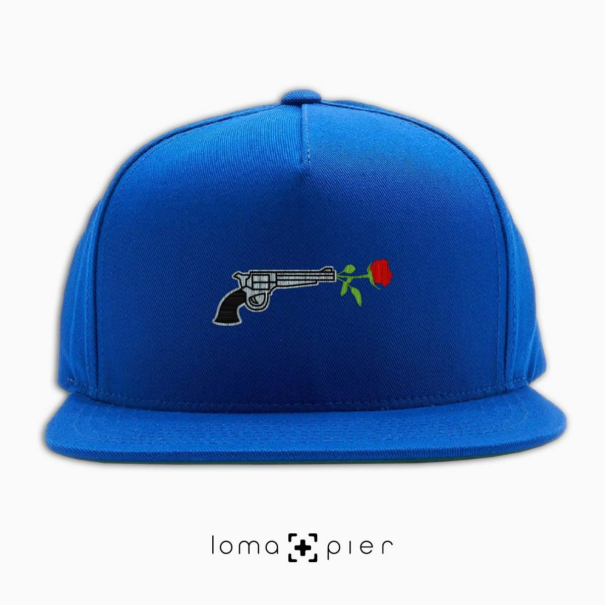 ROSE REVOLVER icon embroidered on a royal blue and red classic snapback hat with multicolor thread by loma+pier hat store