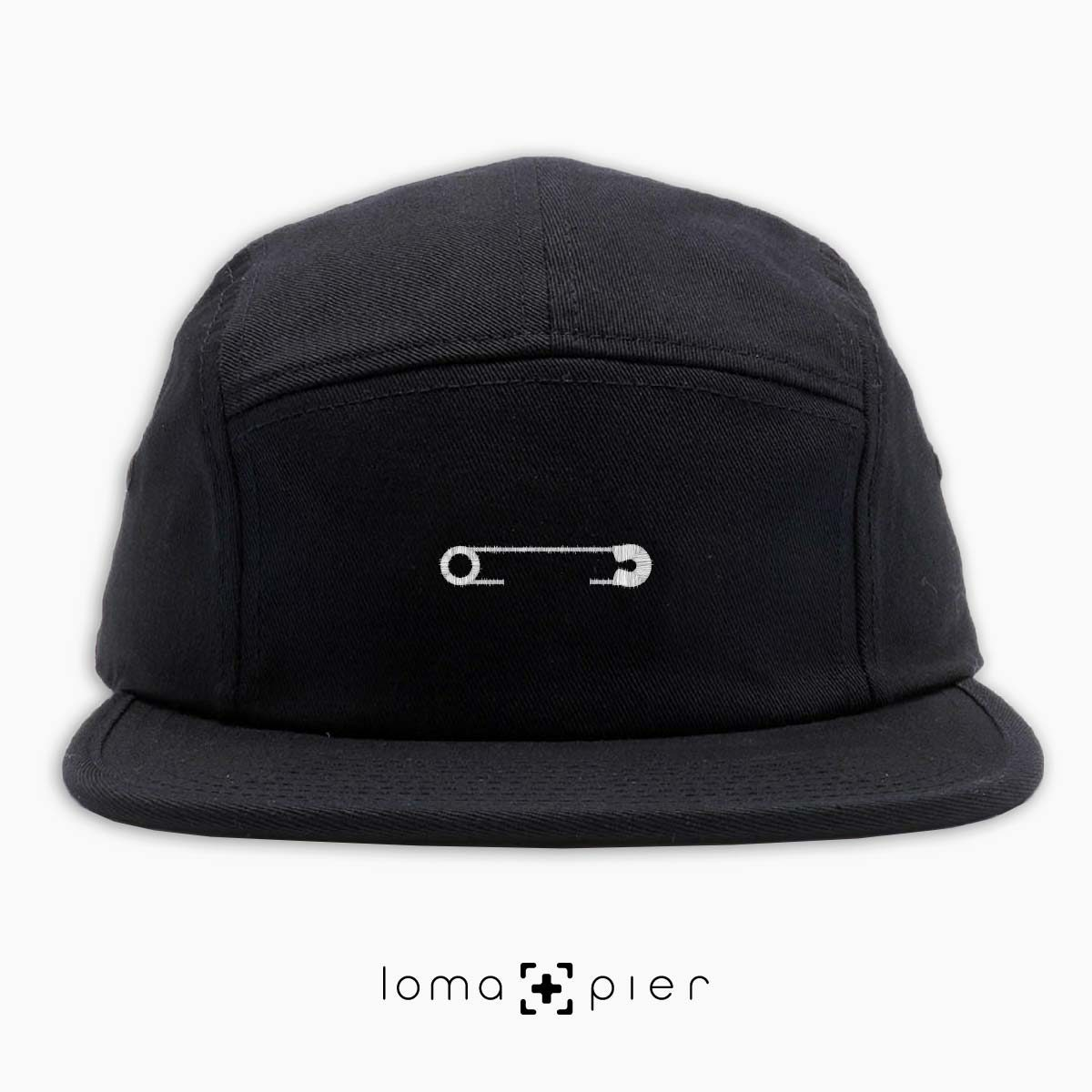 SAFETY PIN icon embroidered on a black cotton 5-panel hat with white thread by loma+pier hat store