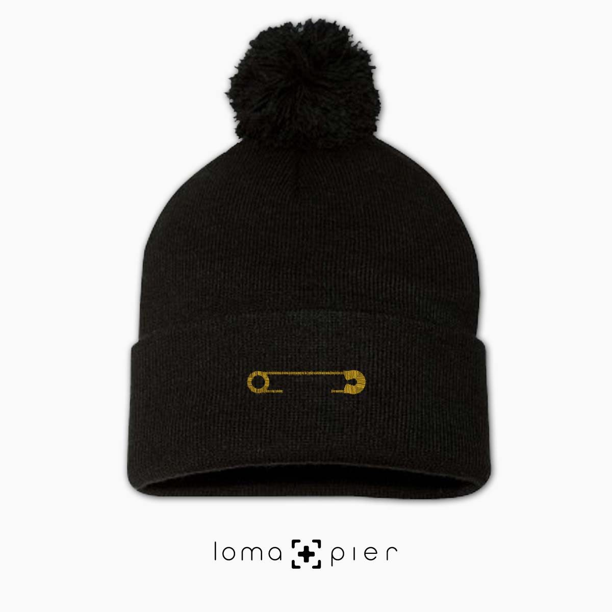 SAFETY PIN icon embroidered on a black pom pom beanie with gold thread by loma+pier hat store