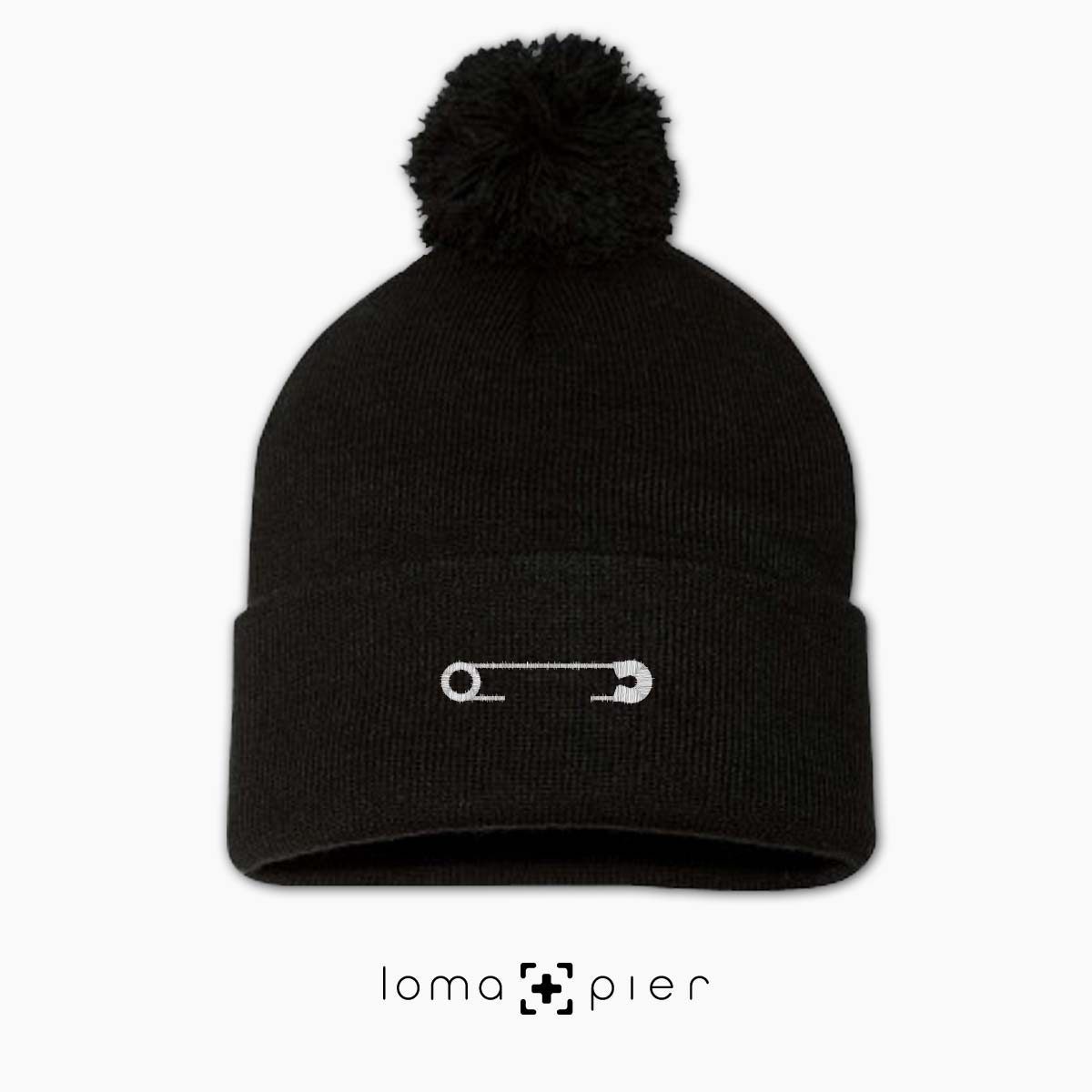 SAFETY PIN icon embroidered on a black pom pom beanie with white thread by loma+pier hat store