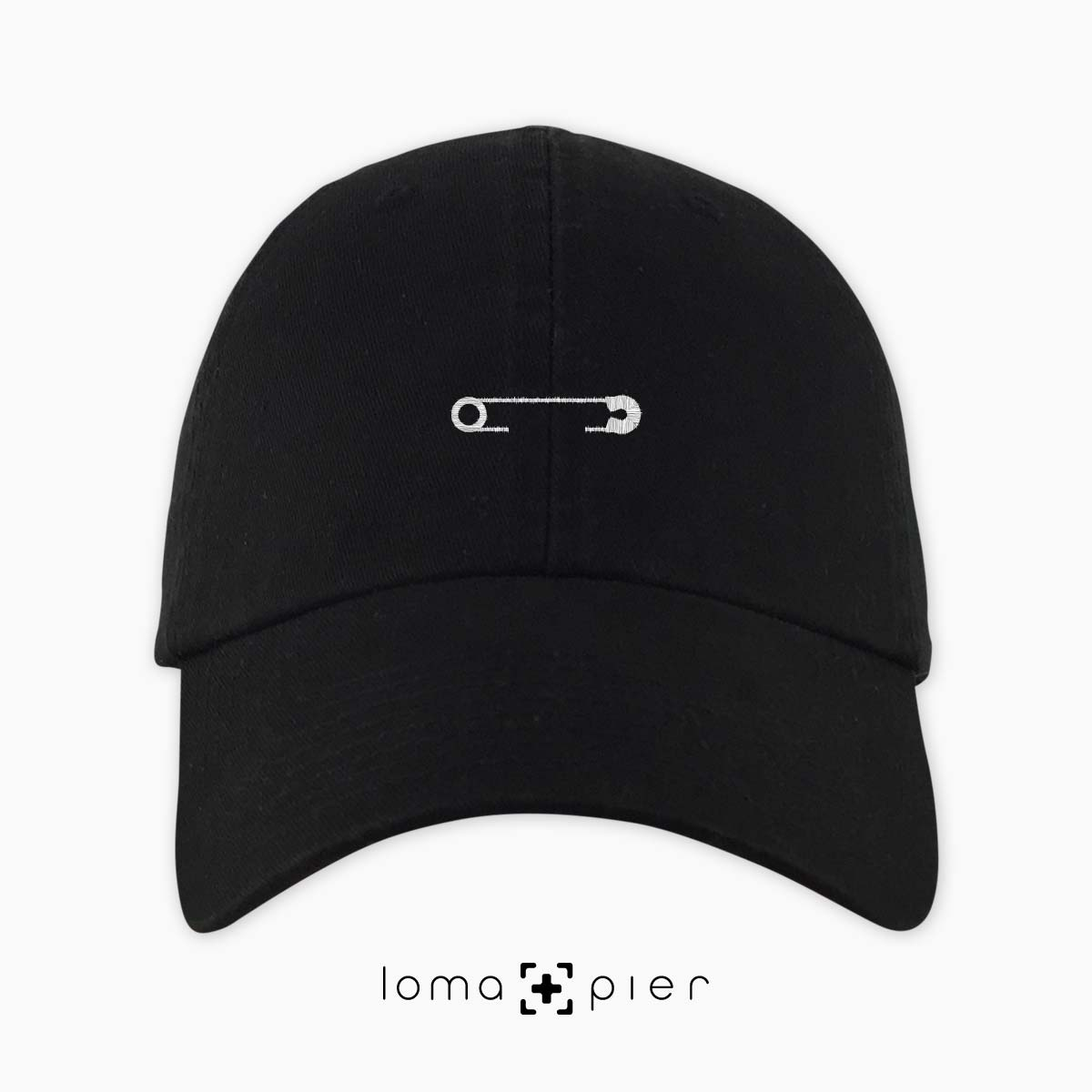 SAFETY PIN icon embroidered on a black unstructured dad hat with white  thread by loma+ 61396e4f3b2