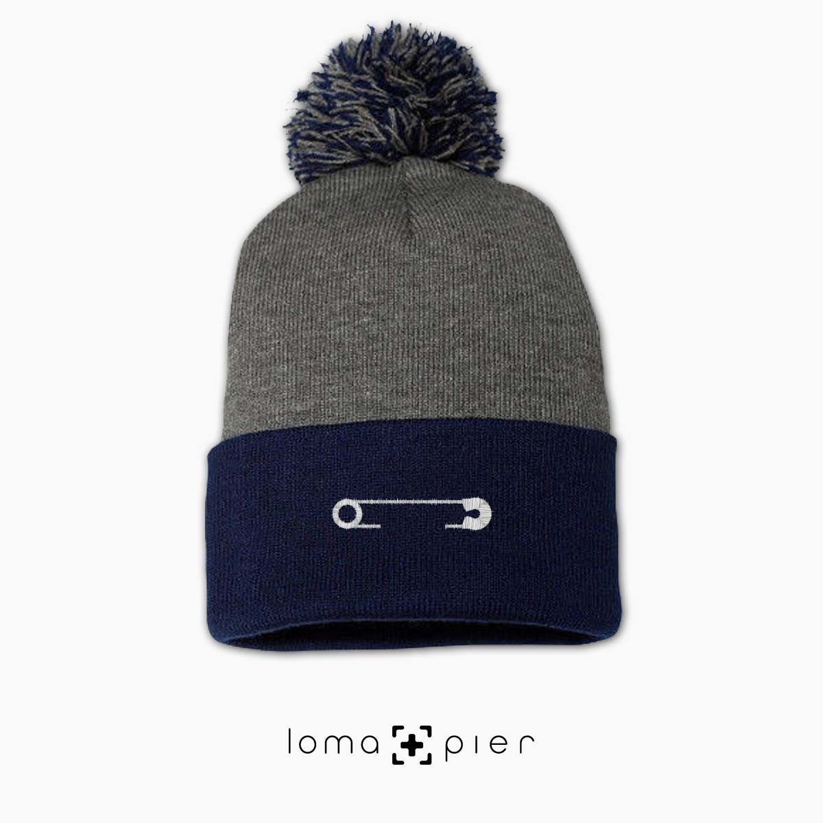 SAFETY PIN icon embroidered on a heather grey and navy blue pom pom beanie with white thread by loma+pier hat store