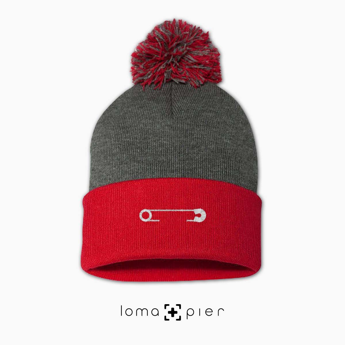 SAFETY PIN icon embroidered on a heather grey and red pom pom beanie with white thread by loma+pier hat store