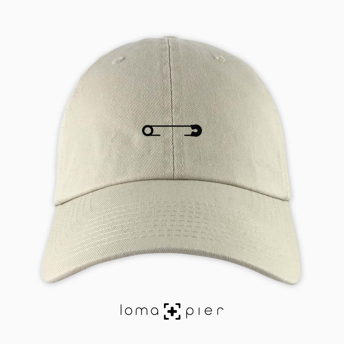 SAFETY PIN icon embroidered on a khaki unstructured dad hat with black thread by loma+pier hat store made in the USA