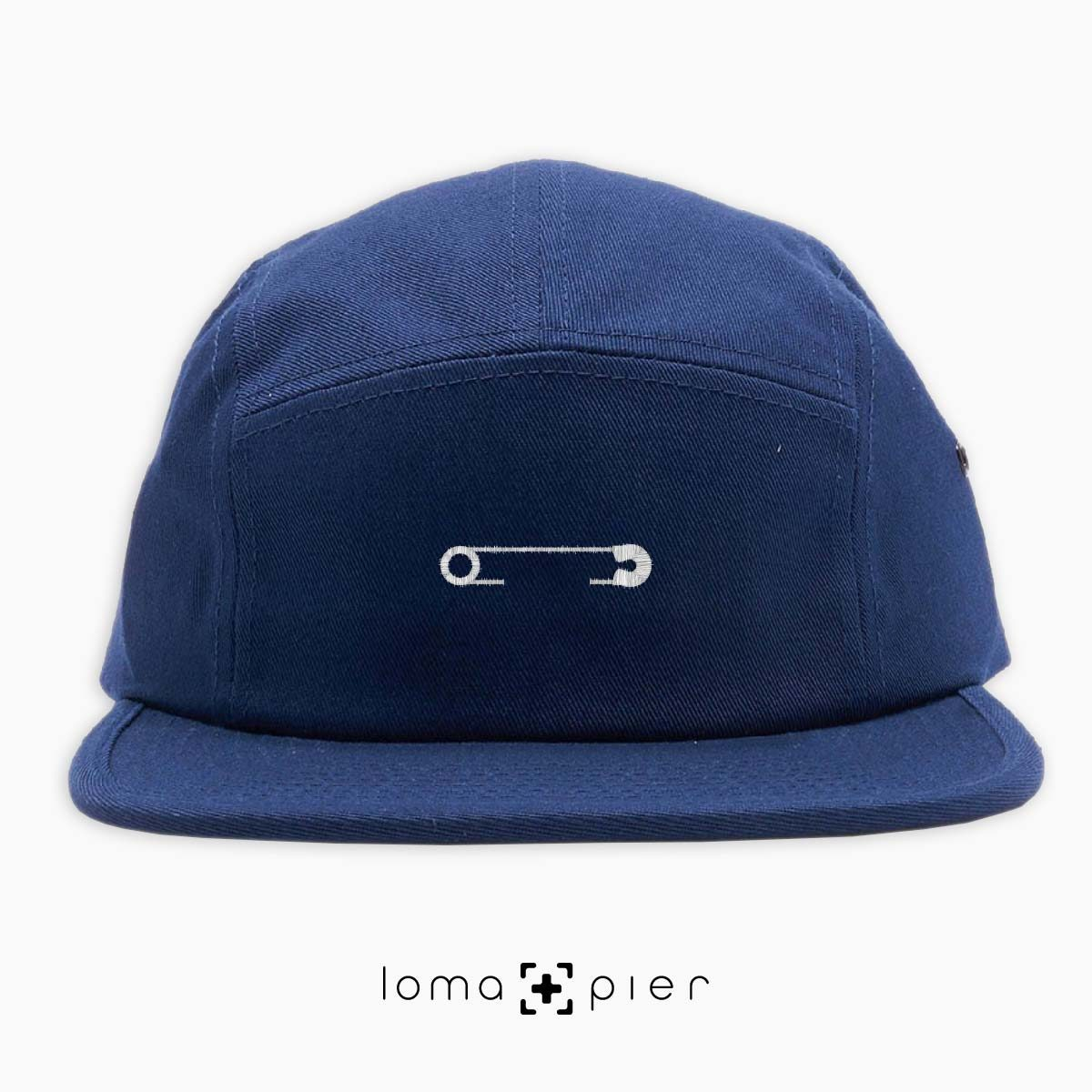 SAFETY PIN icon embroidered on a navy blue cotton 5-panel hat with white thread by loma+pier hat store