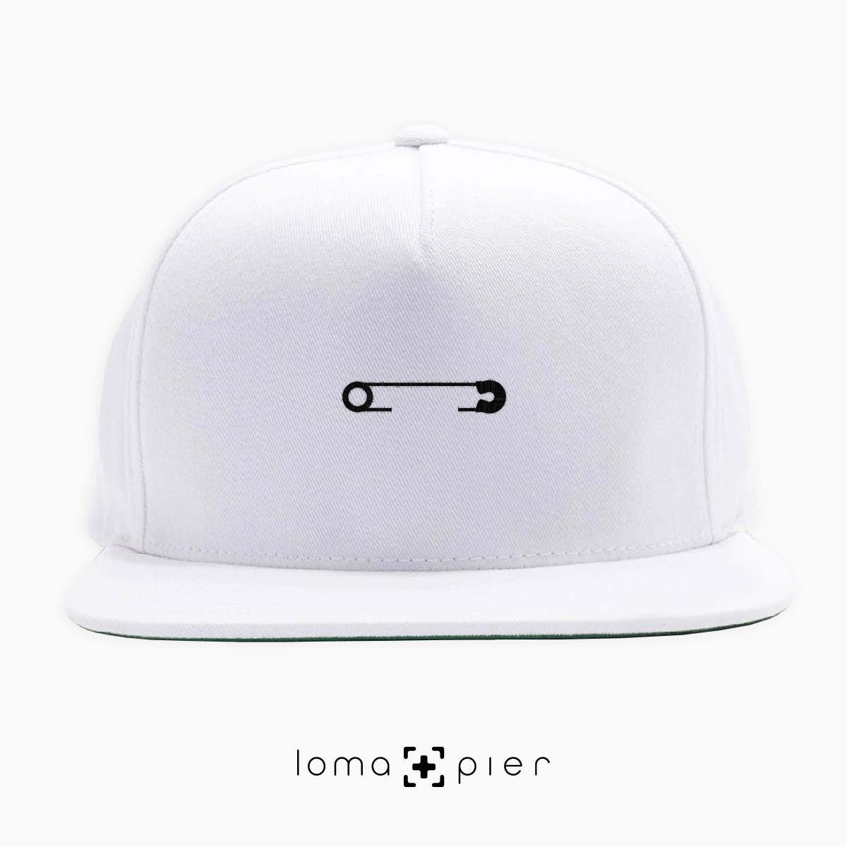SAFETY PIN icon embroidered on a white classic snapback with black thread by loma+pier hat store