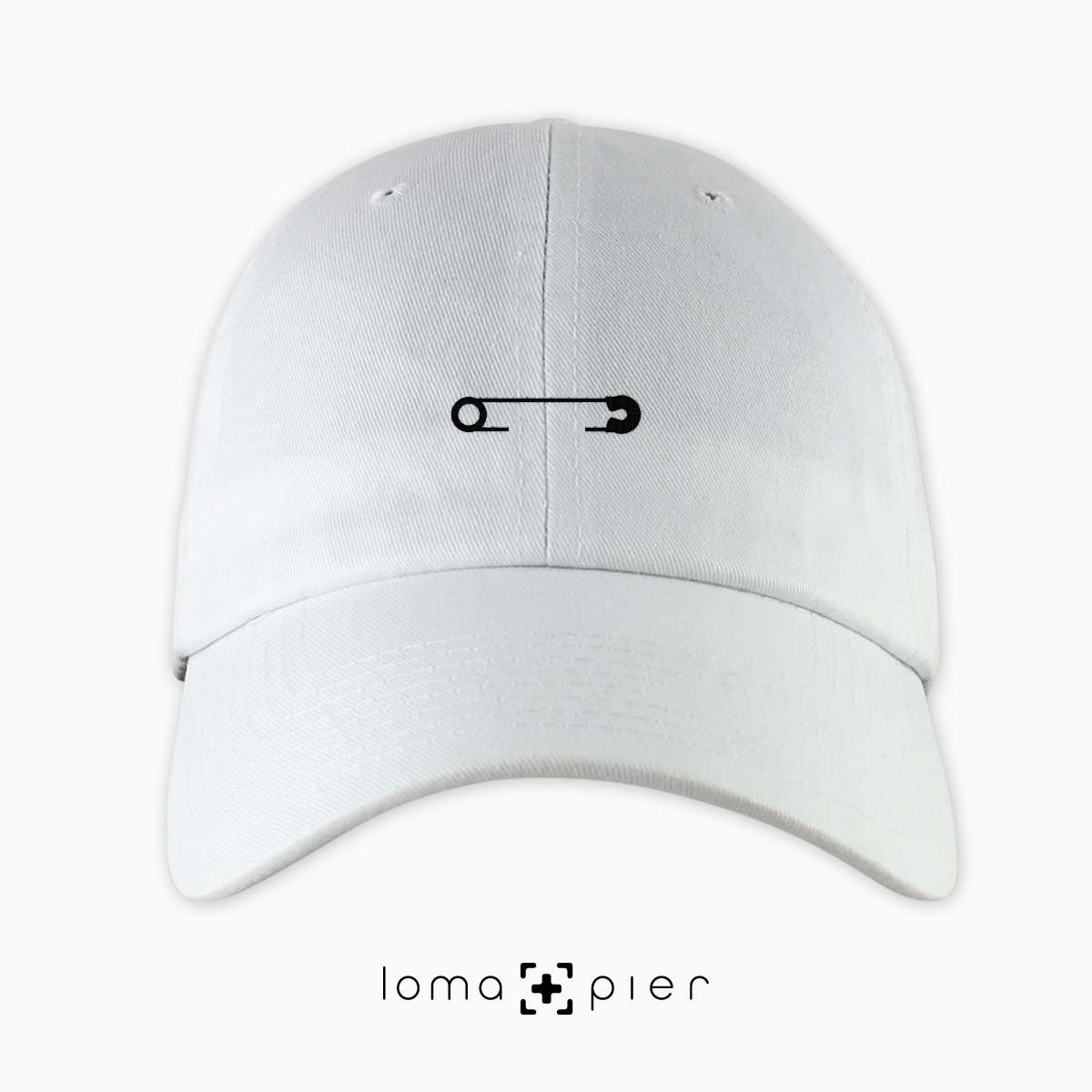 SAFETY PIN icon embroidered on a white unstructured dad hat with black thread by loma+pier hat store made in the USA