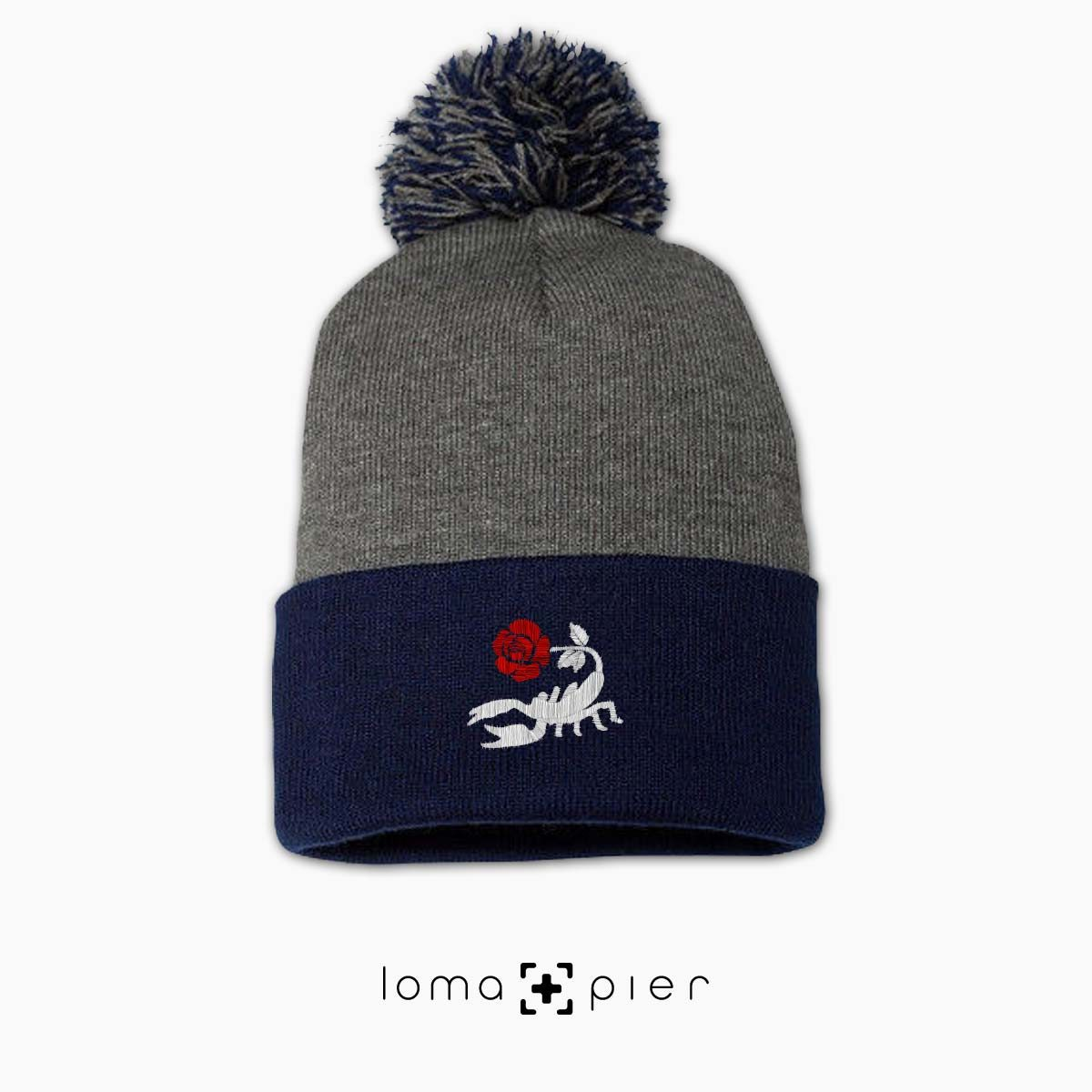 SCORPION ROSE icon embroidered on a heather grey and navy blue pom pom beanie with multicolor thread by loma+pier hat store