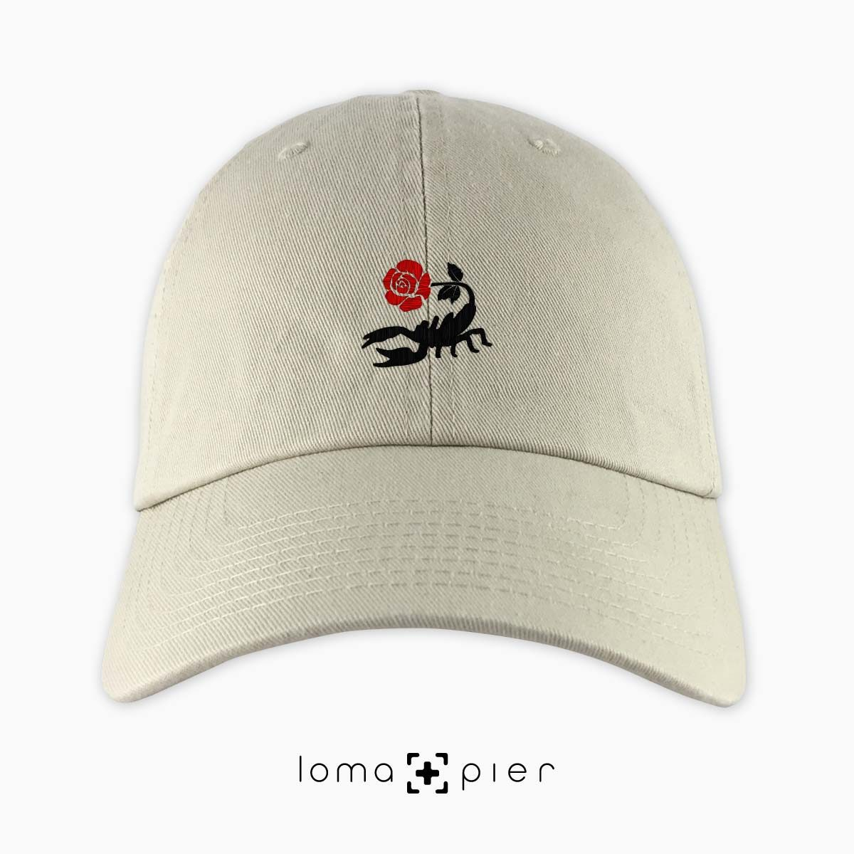 SCORPION ROSE icon embroidered on a khaki unstructured dad hat with red and black thread by loma+pier hat store made in the USA