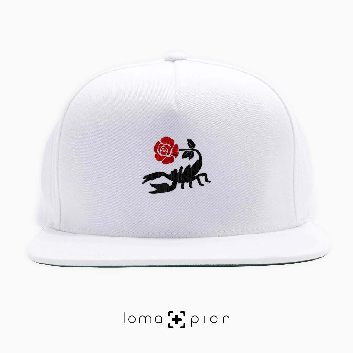 SCORPION ROSE icon embroidered on a white classic snapback hat with multicolor thread by loma+pier hat store