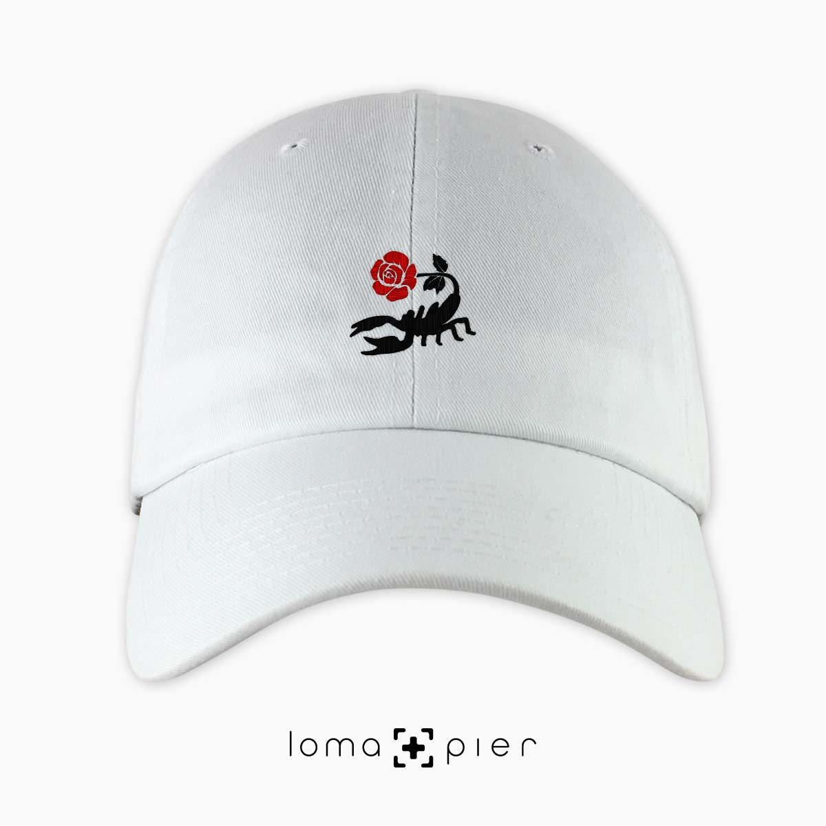 SCORPION ROSE icon embroidered on a white unstructured dad hat with red and black thread by loma+pier hat store made in the USA