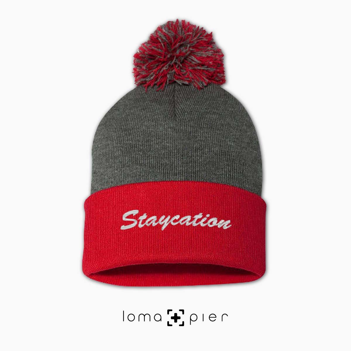 STAYCATION chill saying embroidered on a grey red pom pom beanie by loma+pier hat store