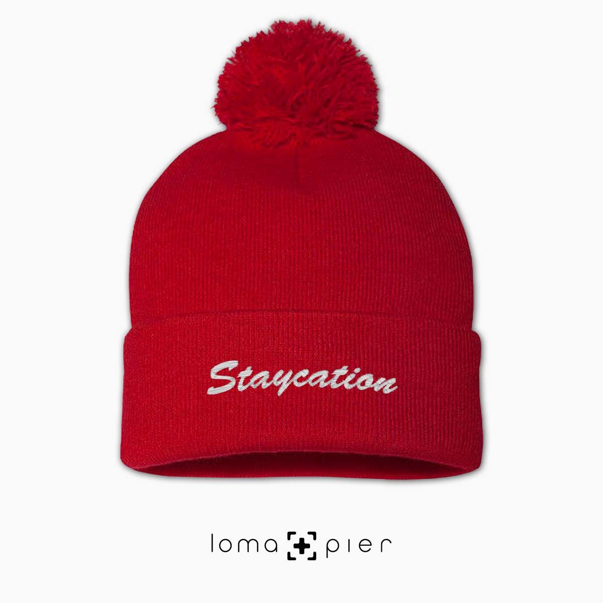 STAYCATION chill saying embroidered on a red pom pom beanie by loma+pier hat store