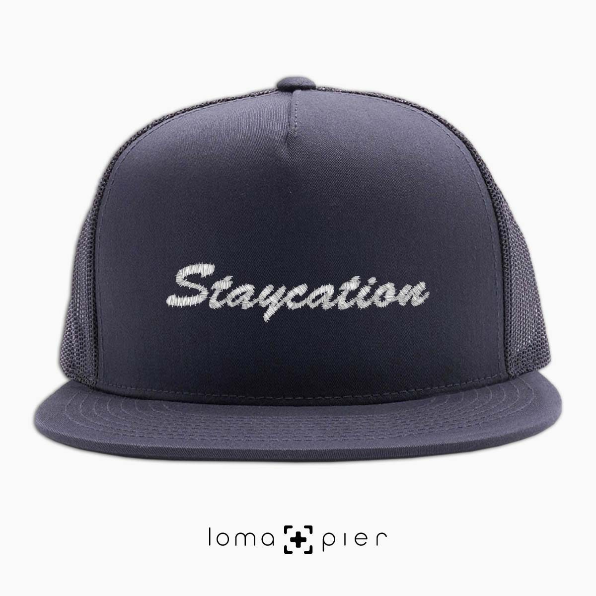 STAYCATION embroidered on a charcoal beach netback trucker by loma+pier hat store