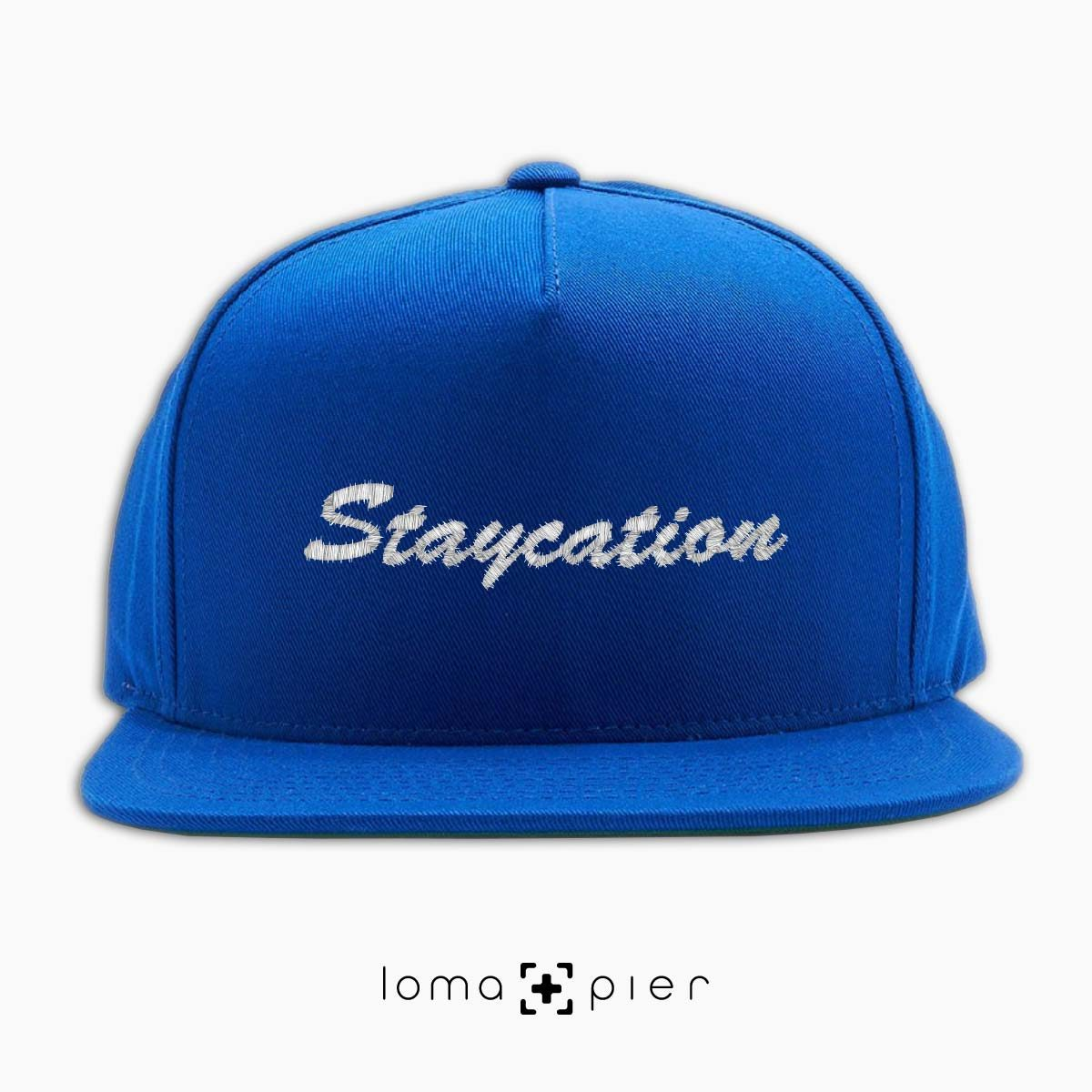 STAYCATION introvert saying embroidered on a royal blue classic snapback hat with white thread by loma+pier hat store