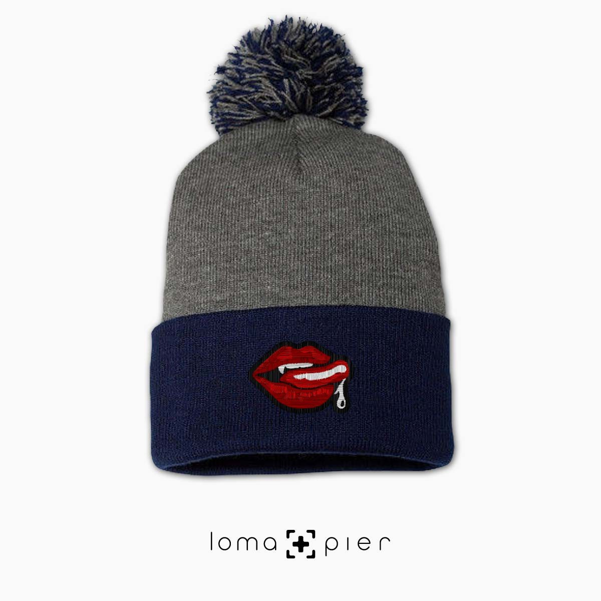 SUCCUBUS icon embroidered on a heather grey and navy blue pom pom beanie with multicolor thread by loma+pier hat store