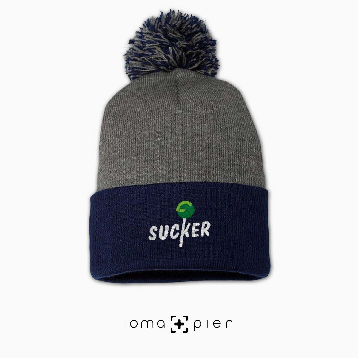 SUCKER icon embroidered on a heather grey and navy blue pom pom beanie with multicolor thread by loma+pier hat store