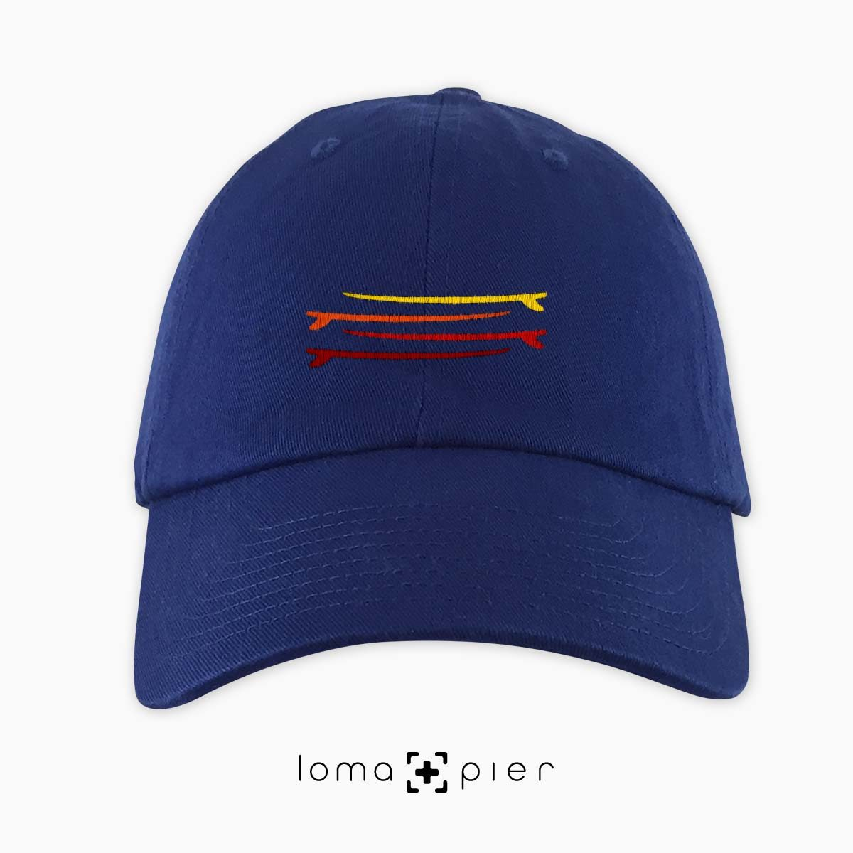 SURFBOARDS STACKED icon embroidered on a blue dad hat by loma+pier hat store made in the USA