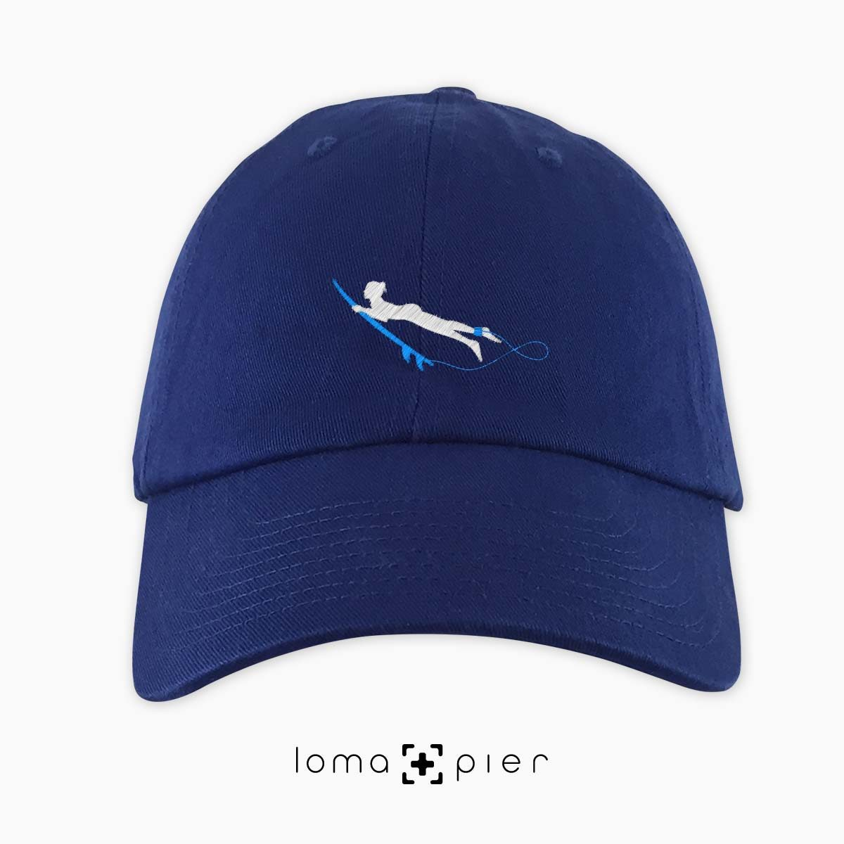 DUCK NAKED SURFER icon embroidered on a royal blue dad hat by loma+pier hat store made in the USA