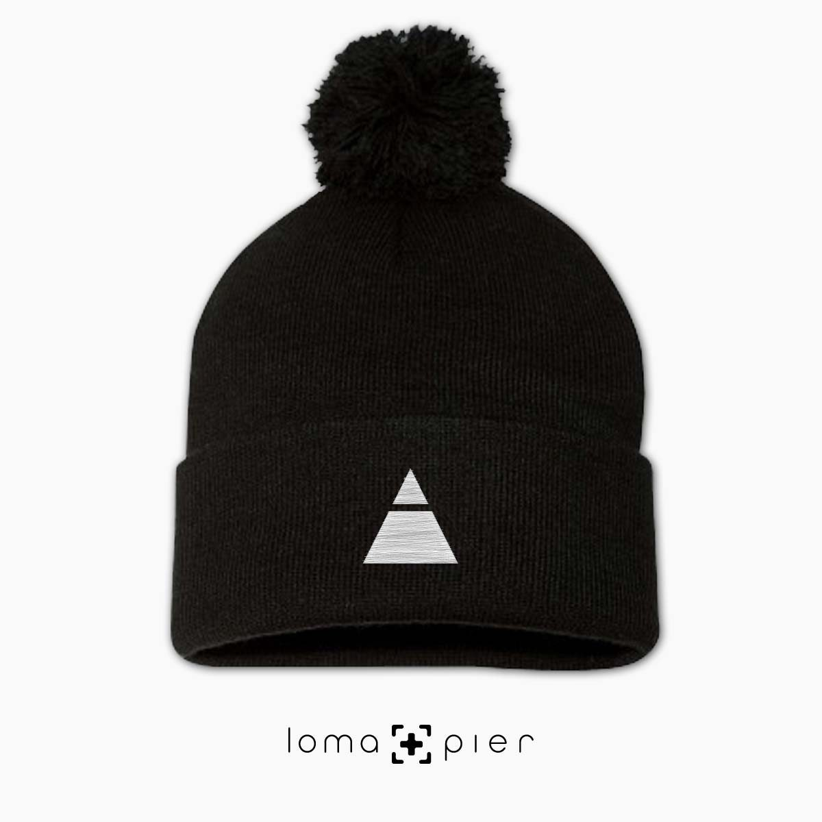 TRYANGLE icon embroidered on a black pom pom beanie with white thread by loma+pier hat store