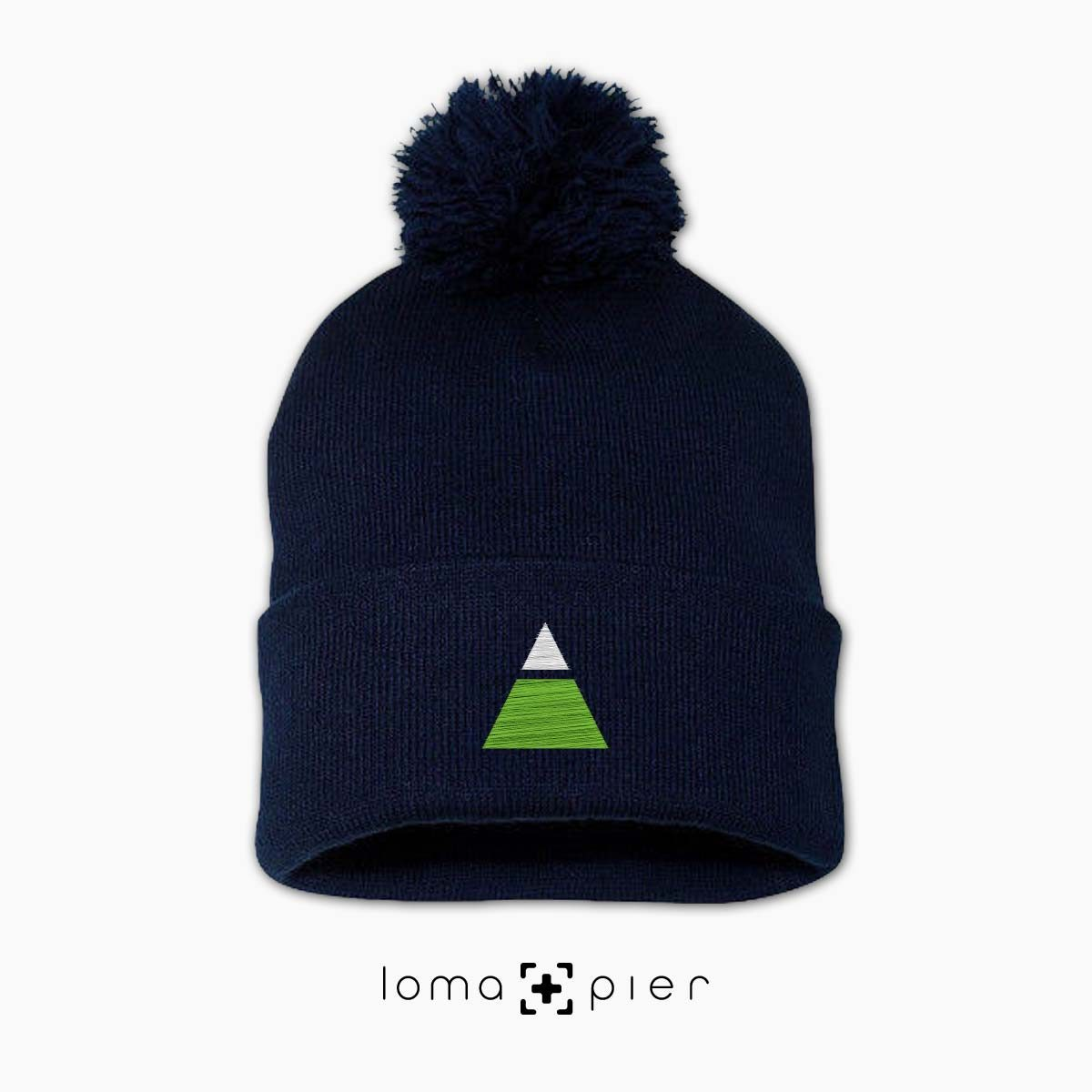 TRYANGLE icon embroidered on a navy blue pom pom beanie with multicolor thread by loma+pier hat store