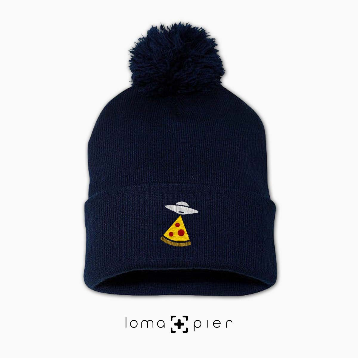 UFO PIZZA icon embroidered on a navy blue pom pom beanie with multicolor thread by loma+pier hat store