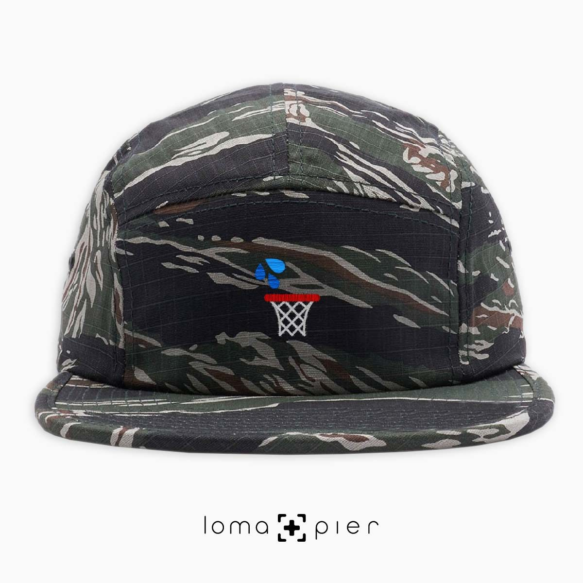 WET JUMPER basketball hoop icon embroidered on a tiger camo cotton 5-panel hat by loma+pier hat store