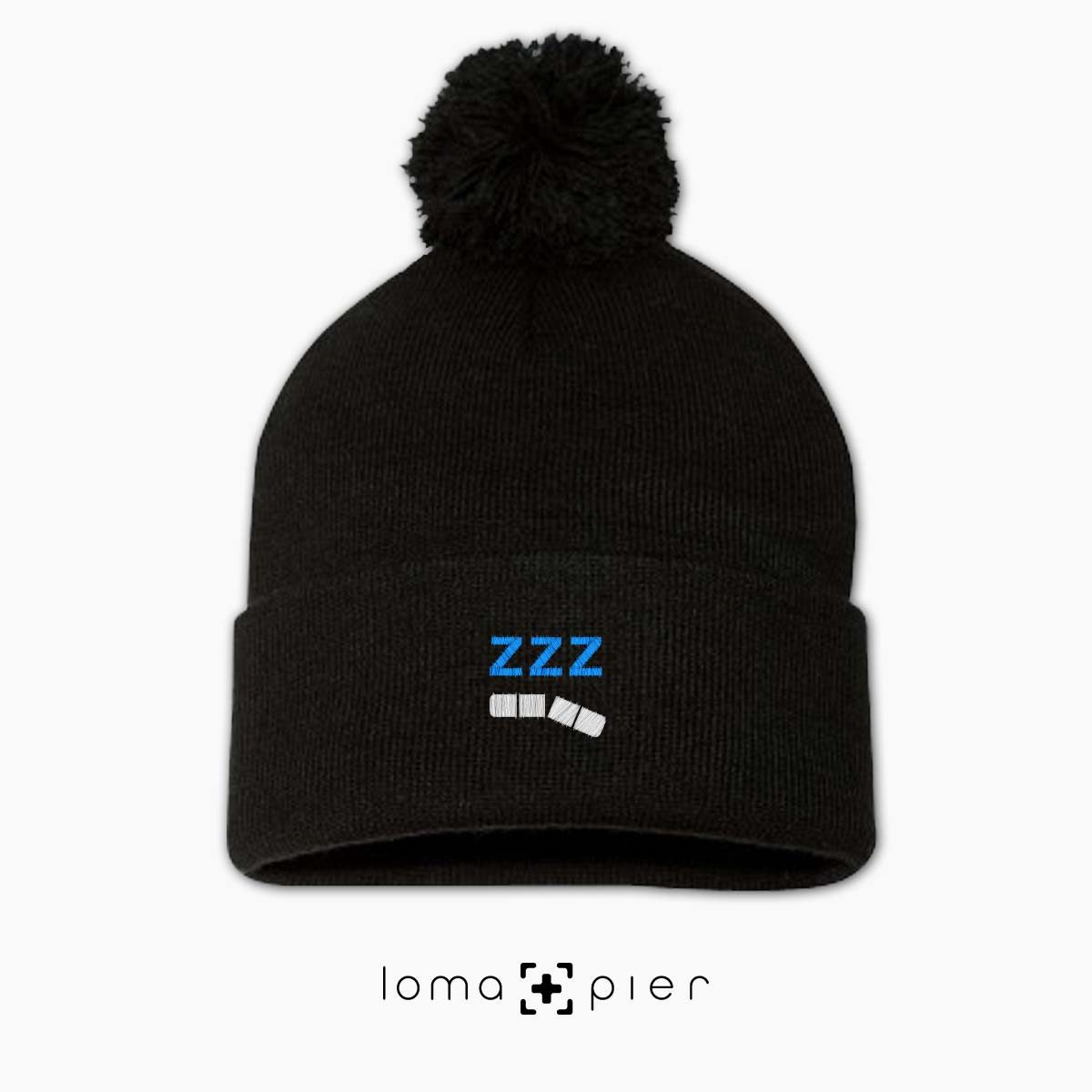 ZZZ-ANNY icon embroidered on a black pom pom beanie with white and sky blue thread by loma+pier hat store