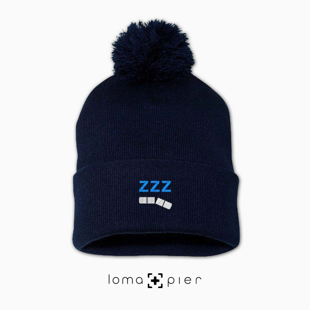 ZZZ-ANNY icon embroidered on a navy blue pom pom beanie with white and sky blue thread by loma+pier hat store
